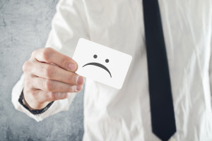 Businessman holding business card with sad face printed